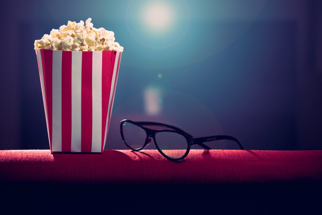 pop corn and glasses on armchair at movies