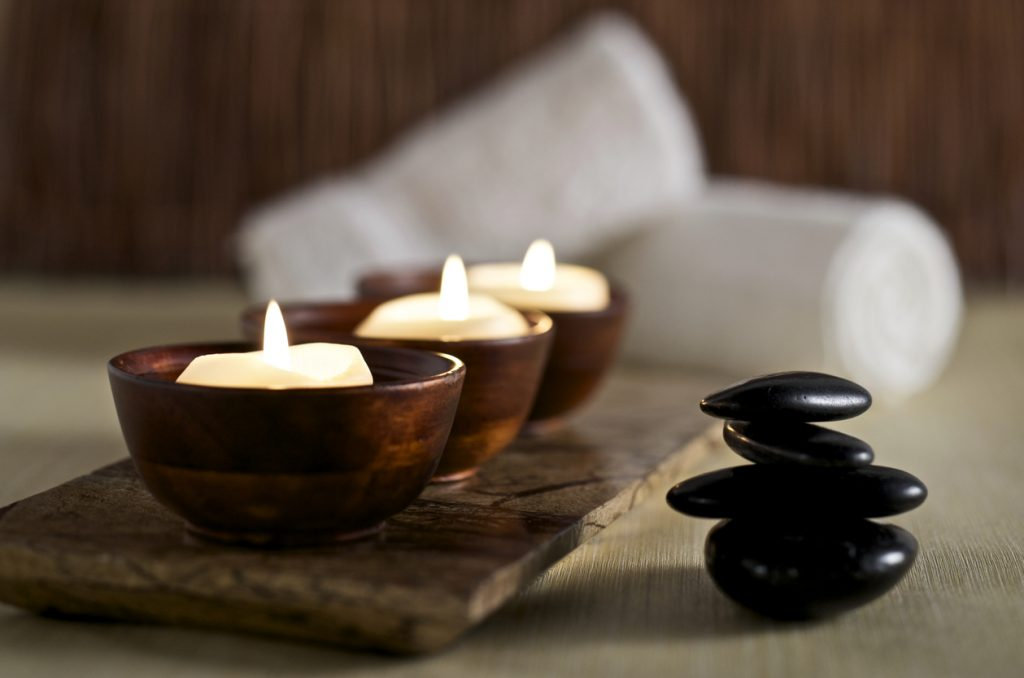 Lit candles and black massage stones for a Zen spa day