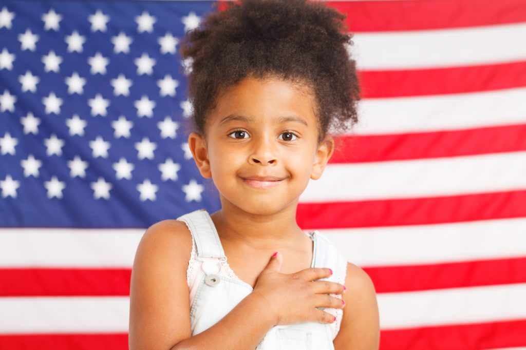 patriotic little girl standing in front of an American flag background
